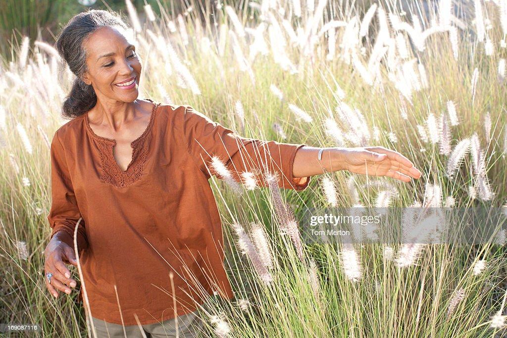 Woman walking in sunny field : Stock Photo