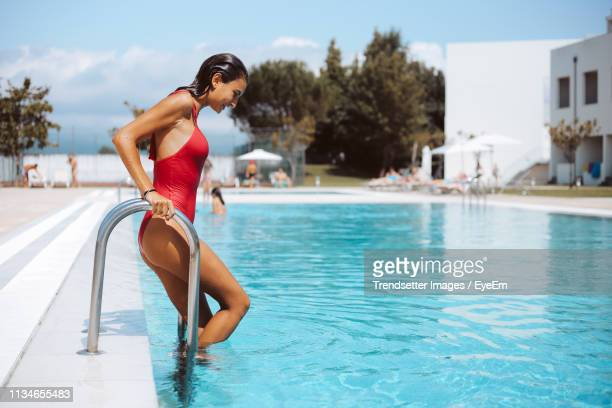 woman walking in swimming pool - swimwear stock pictures, royalty-free photos & images