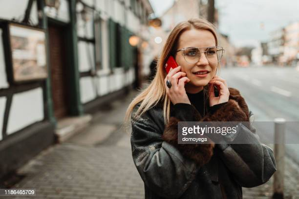 woman walking in the city street and talking on smart phone - dortmund stock pictures, royalty-free photos & images