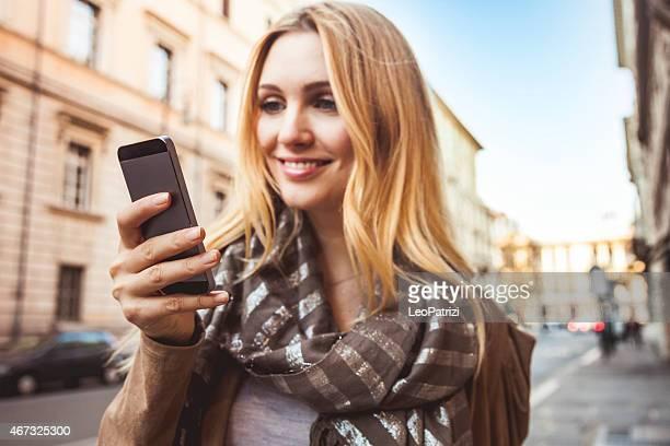 woman walking in the city texting on mobile - mid adult men stockfoto's en -beelden