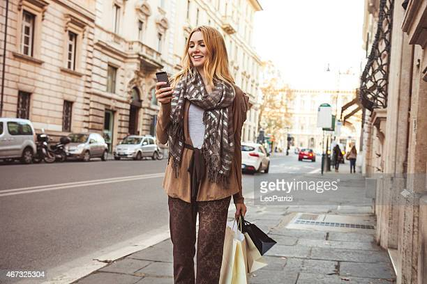 Woman walking in the city texting on mobile