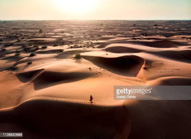 frau zu fuß in die wüste luftaufnahme - persian gulf stock-fotos und bilder