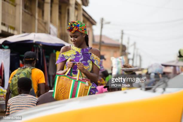 woman walking in the market - ghana stock pictures, royalty-free photos & images