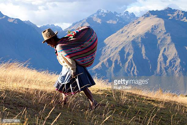 Woman walking in the mountains near the archaeological site of Moray, near Cusco. Peru.