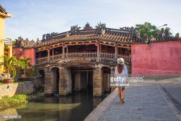woman walking in the old town district of hoi an in vietnam during a sunny day - vietnam stock pictures, royalty-free photos & images