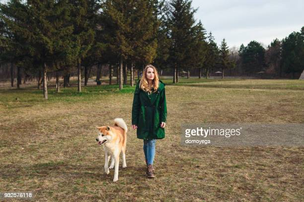 Woman walking in the public park with Akita dog