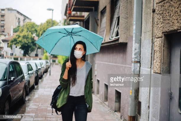 mujer caminando bajo la lluvia durante la pandemia - lluvia fotografías e imágenes de stock