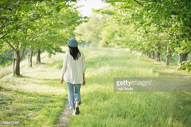 woman walking in the spring breeze - zwart haar stockfoto's en -beelden