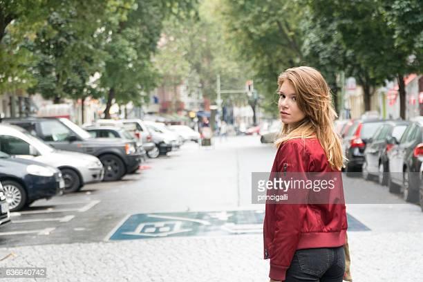 Woman walking in the street looking back
