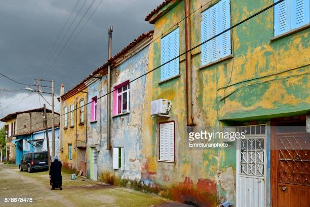 woman walking in the street with colorful painted houses of old town in tire,aegean turkey. - emreturanphoto stock pictures, royalty-free photos & images