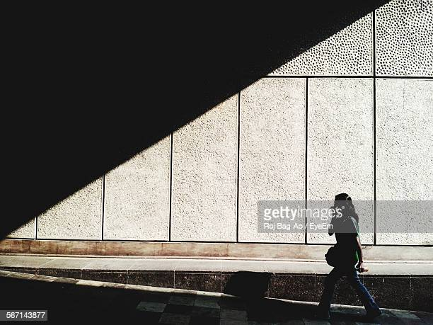 Woman Walking In Tunnel Against Wall