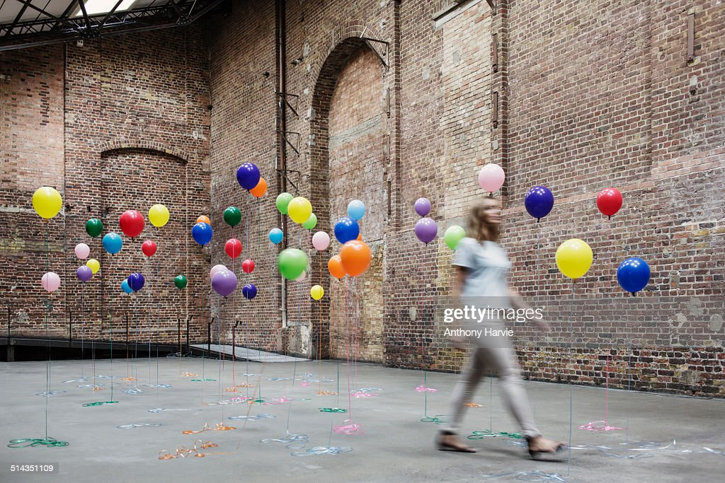 Woman walking in warehouse with colourful balloons : Stock Photo