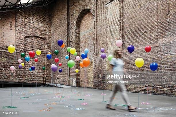 woman walking in warehouse with colourful balloons - same action stock photos and pictures