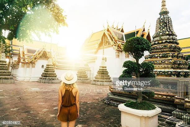 Woman walking in Wat Pho temple at sunrise