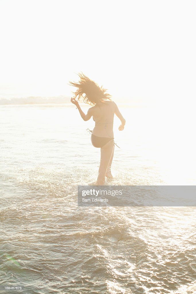 Woman walking in waves on beach : Stock Photo
