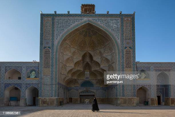 woman walking inside jameh or friday mosque of isfahan, iran - isfahan province stock pictures, royalty-free photos & images