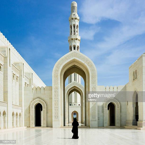 Woman walking inside Sultan Qaboos Grand Mosque Muscat Oman