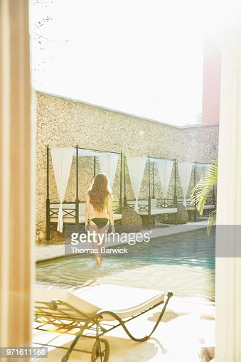 Woman walking into pool in courtyard of boutique hotel