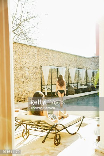 Woman walking into pool in courtyard of boutique hotel while friends relax in lounge chairs