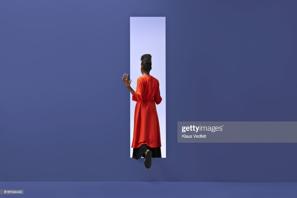 Woman walking into rectangular opening in coloured wall : Photo