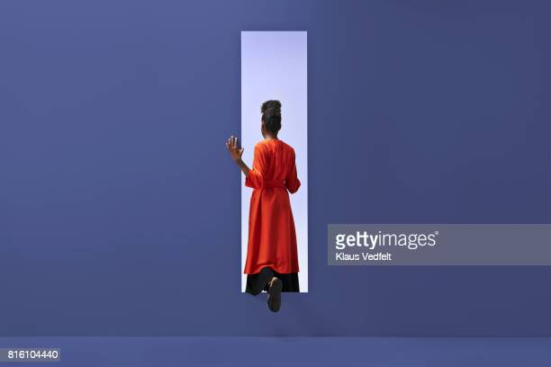 woman walking into rectangular opening in coloured wall - purple dress stock pictures, royalty-free photos & images
