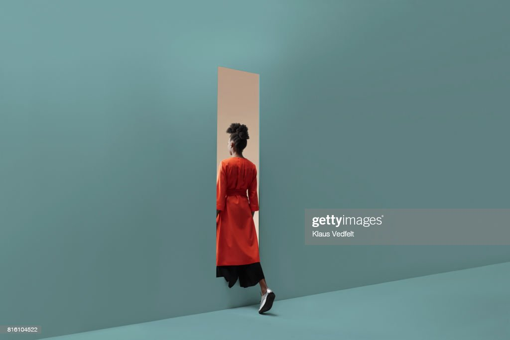 Woman walking into rectangular opening in coloured wall : Stock Photo