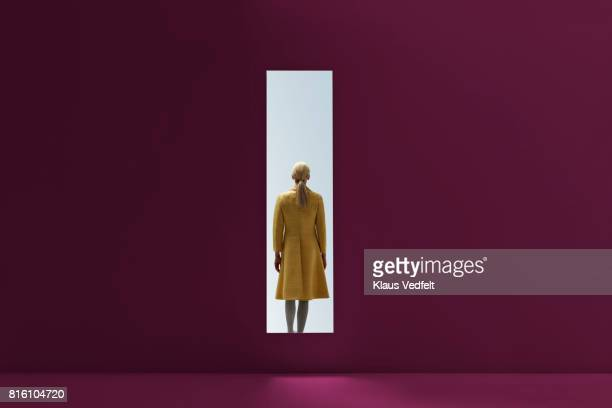 woman walking into rectangular opening in coloured wall - raadsel stockfoto's en -beelden