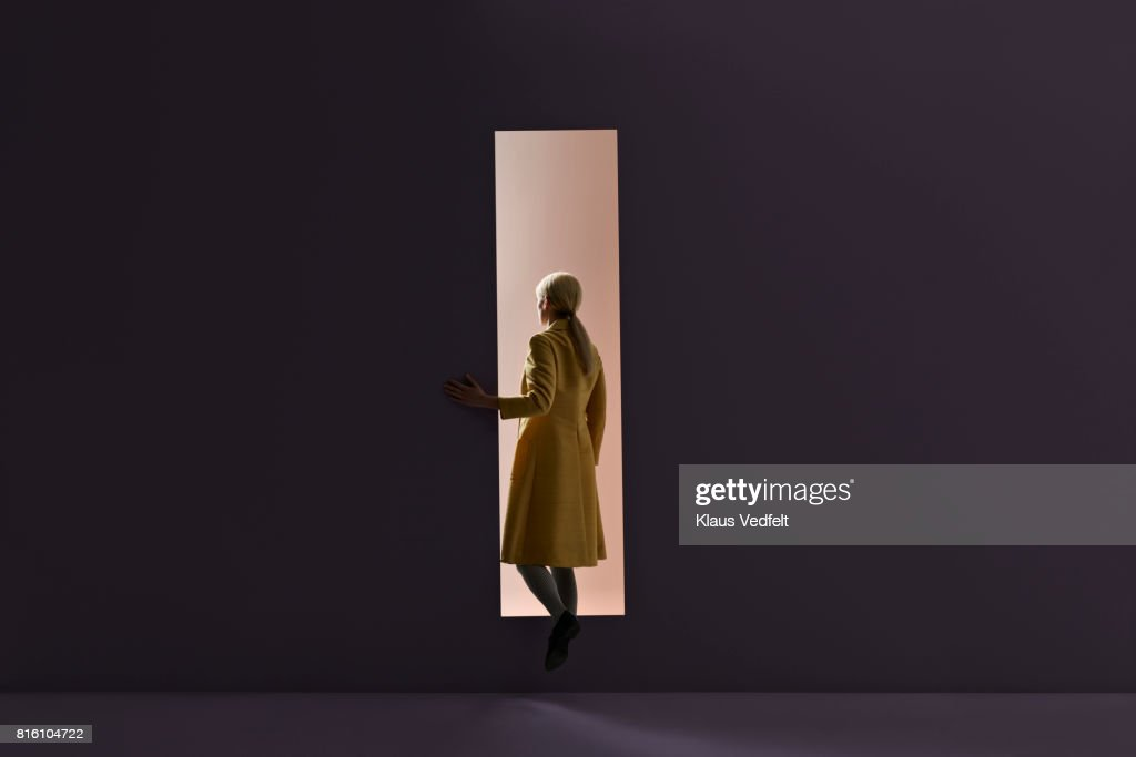 Woman walking into rectangular opening in coloured wall : Stock-Foto