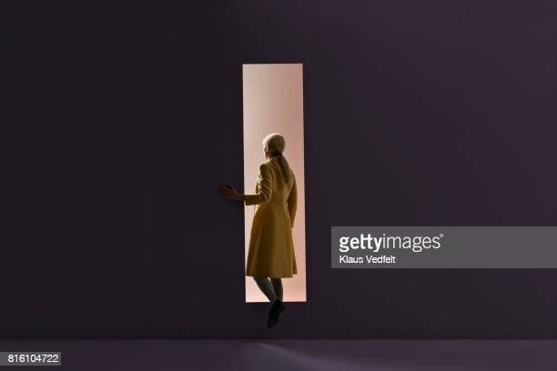 woman walking into rectangular opening in coloured wall - deur stockfoto's en -beelden
