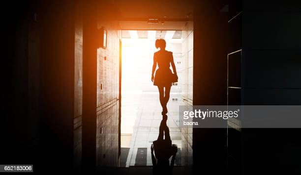 woman walking into the light - doorway stock pictures, royalty-free photos & images