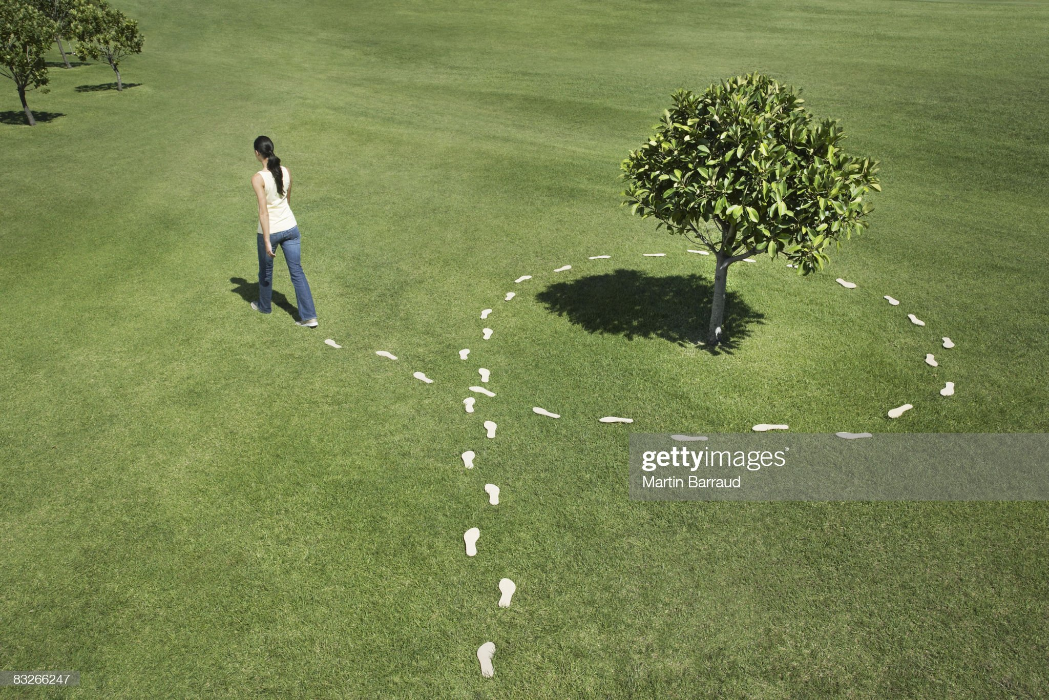 Woman walking leaving trail of footprints : Stock Photo