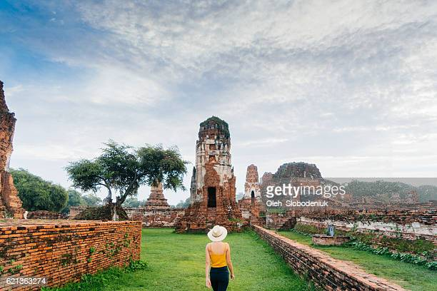 Woman walking near  ancient Buddhist Temple