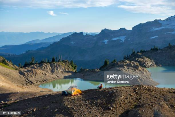a woman walking near her tent site while on a backpacking trip near mt. baker. - bellingham stock pictures, royalty-free photos & images