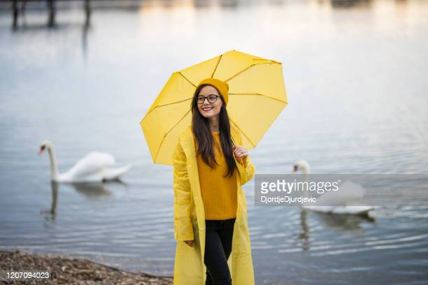 woman walking near lake on rainy day - yellow hat stock pictures, royalty-free photos & images