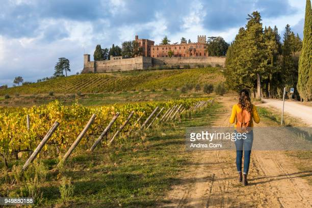 woman walking near the brolio castle. radda in chianti, siena province, tuscany. - only young women stock pictures, royalty-free photos & images
