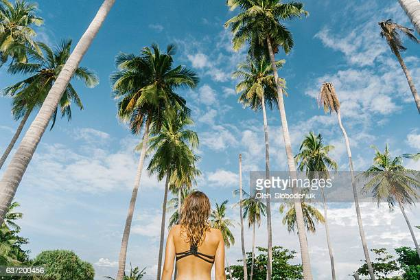 Woman walking near the palm trees