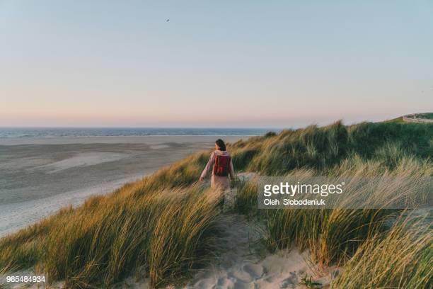 vrouw lopen in de buurt van de zee op texel eiland bij zonsondergang - friesland noord holland stockfoto's en -beelden