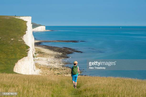 a woman walking near the white chalk cliffs near beachy head on the south downs in england - イーストサセックス ストックフォトと画像