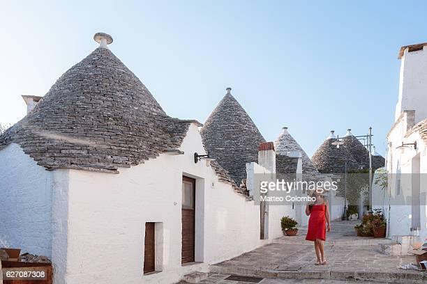 woman walking near trulli houses, alberobello, apulia, italy - alberobello stock photos and pictures