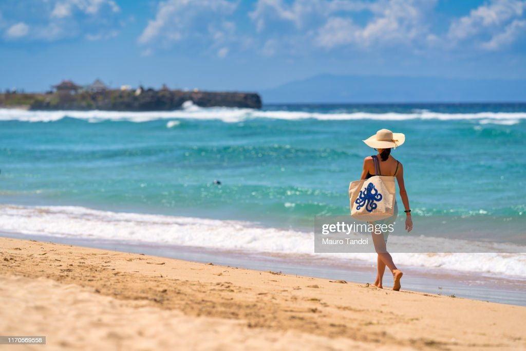 A woman walking nearby to the sea with a beautiful bag, Nusa Dua Beach, Bali, Indonesia : Foto stock
