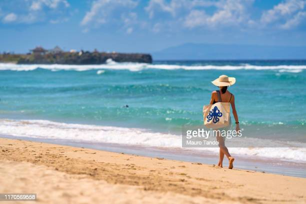a woman walking nearby to the sea with a beautiful bag, nusa dua beach, bali, indonesia - mauro tandoi stock photos and pictures