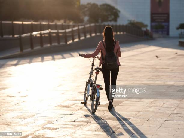 woman walking next to bike in city - next to stock pictures, royalty-free photos & images