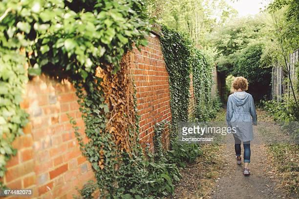 Woman Walking Next To Brick Wall
