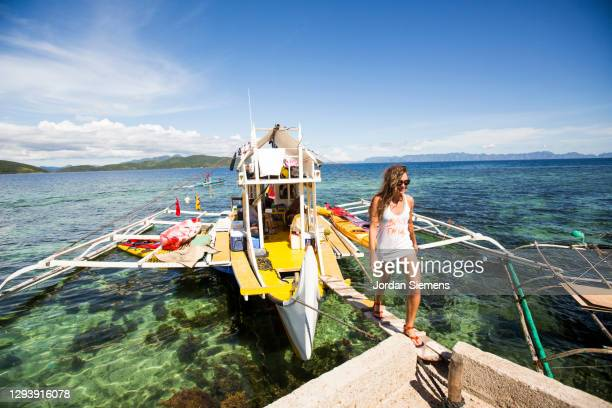 a woman walking off a bunk boat in the philippines while on a kayaking excursion. - capital region stock pictures, royalty-free photos & images