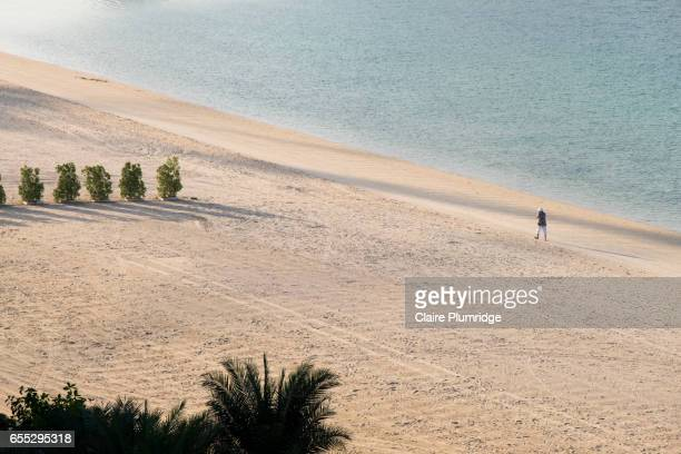 Woman walking on a beach in Dubai early in the morning, taken from a high view.