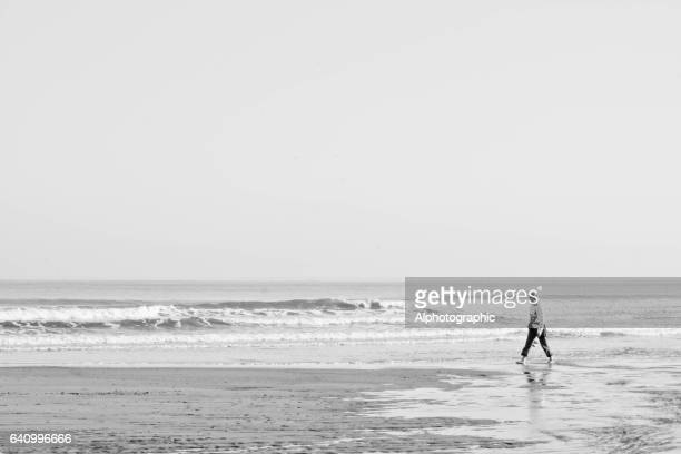 woman walking on a beach - reflection pool stock pictures, royalty-free photos & images