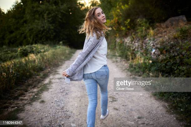 woman walking on a dirt track in the countryside turning round - abschied stock-fotos und bilder