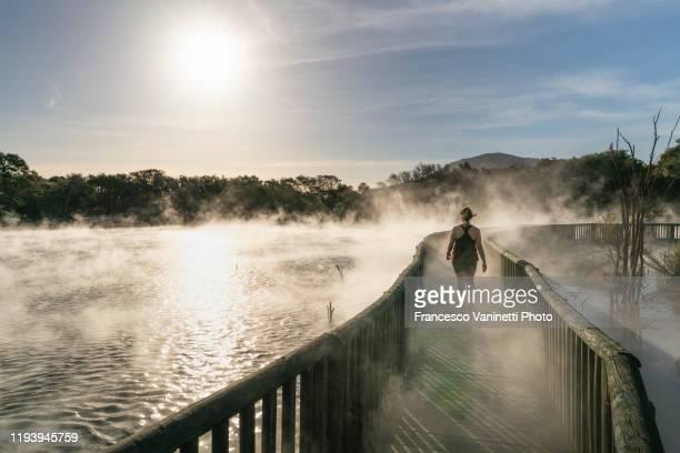 woman walking on a footpath at kuirau park, rotorua, nz. - rotorua stock pictures, royalty-free photos & images