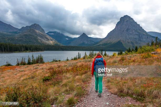 woman walking on a hiking trail, two medicine lake, glacier national park, montana, usa - two medicine lake montana stock photos and pictures