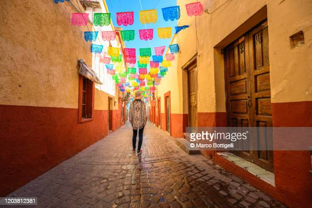 woman walking on a narrow colorful alley in guanajuato, mexico - guanajuato stock pictures, royalty-free photos & images